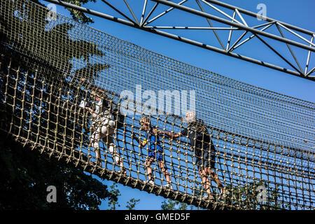 Child with grandparents walking over rope bridge / swing bridge / suspended bridge at canopy tour in adventure park - Stock Photo