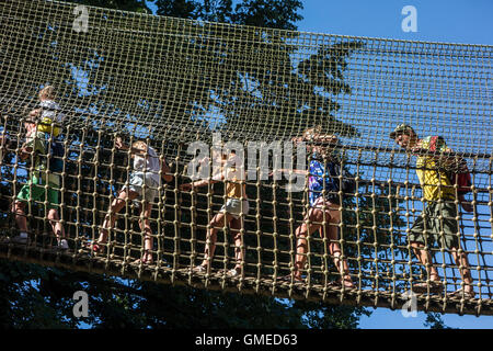 Parents with kids walking over rope bridge / swing bridge / suspended bridge at ropes course in adventure park in - Stock Photo