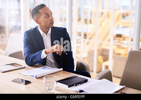 well groomed businessman sitting at conference table in tailored suit - Stock Photo