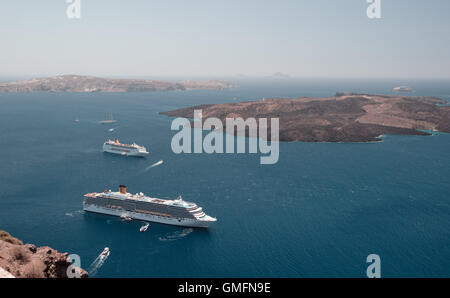SANTORINI, GREECE - JULY 21, 2016: Cruise liners at anchor with little motor boats in the lagoon of Santorini. - Stock Photo