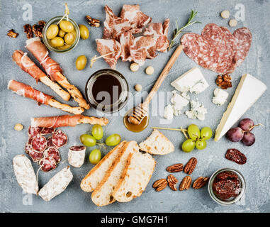 Cheese and meat appetizer selection or wine snack set. Variety of  cheese, salami, prosciutto, bread sticks, baguette, - Stock Photo