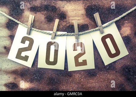 The word '2020' stamped on cards and pinned to an old piece of twine over a rusted metal background. - Stock Photo