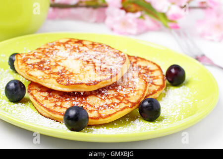 pancakes with powered sugar and blueberries. - Stock Photo