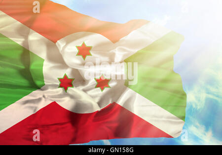 Burundi waving flag against blue sky with sunrays - Stock Photo