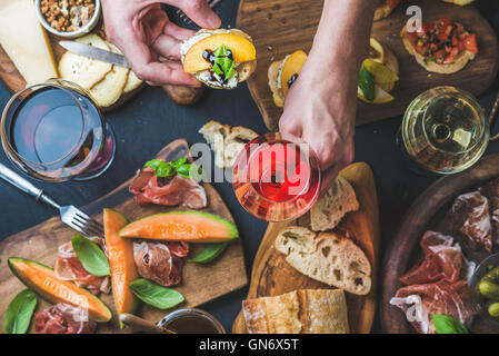 Italian wine snack variety, man's hands holding glass of rose - Stock Photo