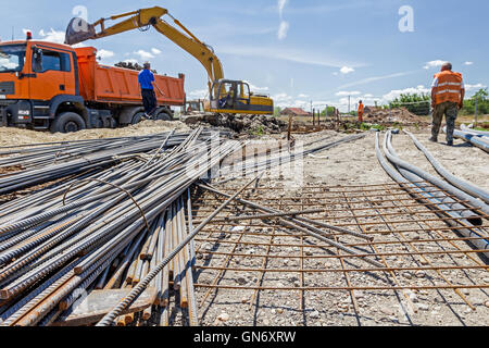 View on rusty square reinforcement for concrete, steel bars, construction site is in background. - Stock Photo