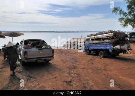 Champasak, Crossing The Mekong River With Trucks and Cargo - Stock Photo