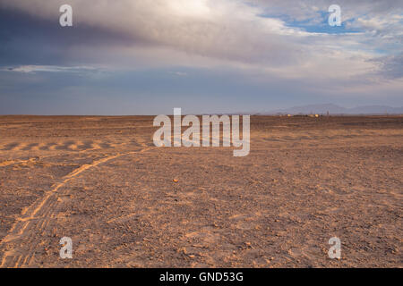 Plane sandy terrain in the desert in Egypt, close to the coast and city Hurghada. Line of mountains in the background. - Stock Photo