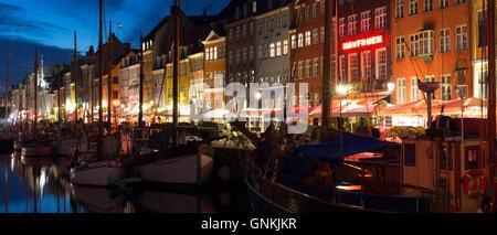 Nightlife in the famous Nyhavn, old canal harbour in Copenhagen on Zealand, Denmark - Stock Photo