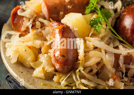 Homemade German Sausage and Sauerkraut with a Pretzel Roll - Stock Photo