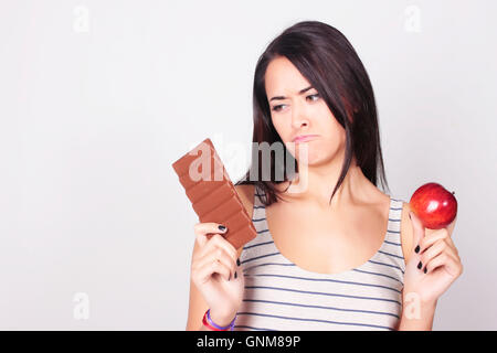 Young caucasian woman making a choice between chocolate and apple. Fitness and diet concept. - Stock Photo