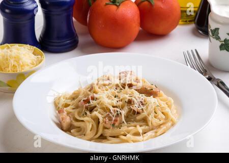 spaghetti carbonara on white table in white plate - Stock Photo