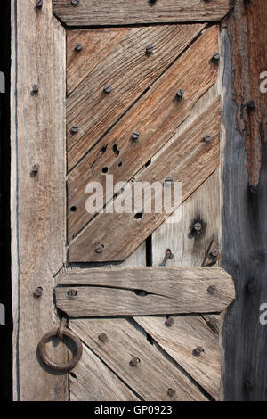 Rusty screw in old wooden door with iron handle. Abstract pattern background. - Stock Photo
