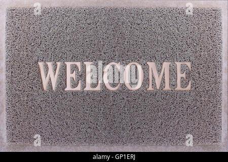 Welcome Door Mat Isolated. Friendly Grey Door Mat Closeup. Welcome Carpet. Foot Scraper Texture Background. - Stock Photo