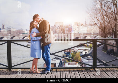 romantic date, young couple kissing on the bridge in Paris - Stock Photo