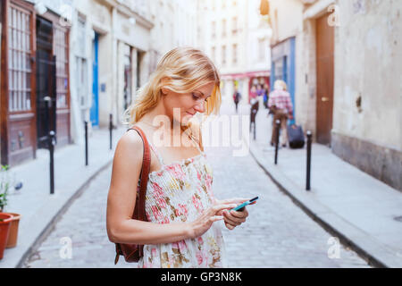 woman using mobile on the street, smart phone application - Stock Photo