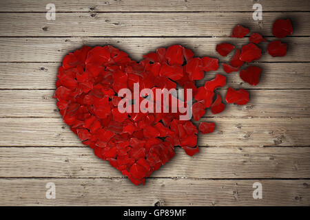 Red rose petals arranged in shape of a broken heart on wooden table. Broken heart breakup concept separation and - Stock Photo