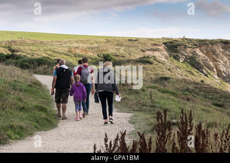 Holidaymakers walk along the South West Coastal Path in the North Cornwall coast. - Stock Photo