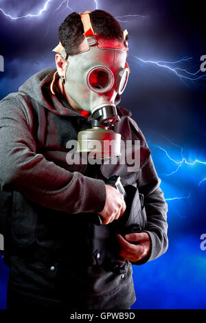 Man with long leather jacket and assault rifle over storm backgr - Stock Photo