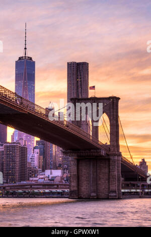 Sunset shot of the Brooklyn Bridge and One World Trade Center seen from the Brooklyn side of the bridge in New York. - Stock Photo