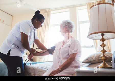 Female nurse doing blood pressure measurement of a senior woman patient. Doctor checking blood pressure of an elderly - Stock Photo