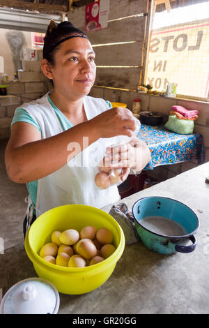 Selling Eggs by the Baggie. A fast food vendor packs up half a dozen brown eggs for a customer in her small cooking - Stock Photo