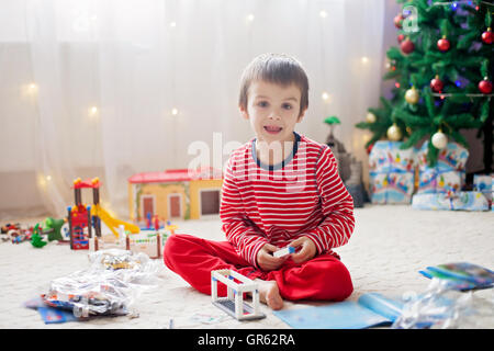 Two sweet children, boy brothers, opening presents on Christmas day, still in pajamas. Kids happiness - Stock Photo