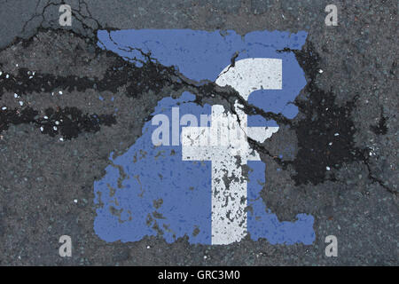 Eroding Facebook Logo On A Road - Stock Photo