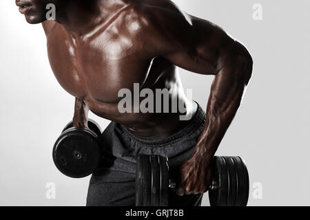 Close up shot of african bodybuilder exercising with dumbbells. Young man doing exercise with heavy dumbbells over - Stock Photo