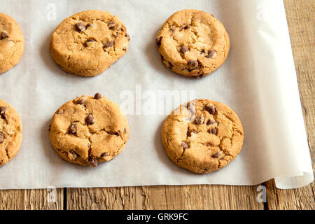 Chocolate chip cookies on baking paper and rustic wooden table - Stock Photo