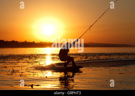 a wakeboard, athlete silhouette on sunset background - Stock Photo