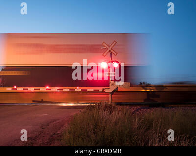 Freight by rail Canadian Pacific Railway speeding through a level crossing, Maple Creek, Saskatchewan, Canada. - Stock Photo