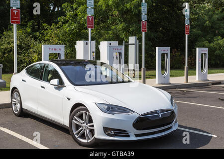 A Tesla Model S automobile gets a charge from a Tesla supercharger charging station at a highway rest stop. - Stock Photo