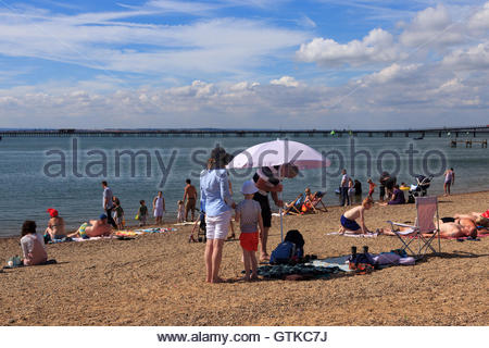 A family are on the busy Jubilee Beach in Southend-On-Sea, Essex. The father is pushing a parasol into the shingle - Stock Photo