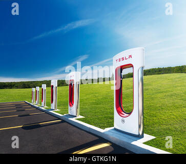 Tesla Supercharger new charging station with green nature scenery and blue sky in the background. Muskoka, Ontario, - Stock Photo