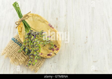 Lavender soap and flower branches bouquet on wooden table - Stock Photo
