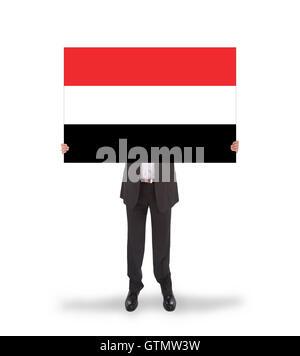 Businessman holding a big card, flag of Yemen - Stock Photo