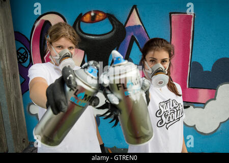 Rosstal, Germany. 30th Aug, 2016. Sonja (L) and Tanja, participants in a graffiti workshop, pose with spray cans - Stock Photo