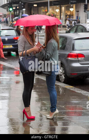 London, UK. 10th Sep, 2016. Weekend shoppers shelter from the rain in High Street Kensington on a wet day in London - Stock Photo