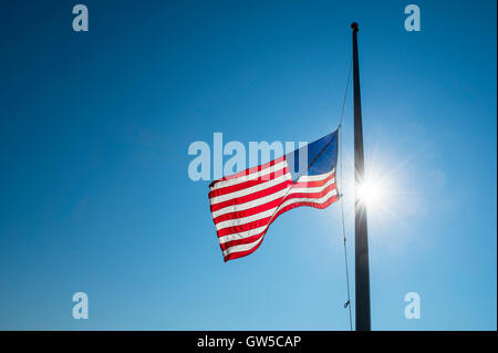 American flag flies at half mast backlit by the sun in bright blue sky - Stock Photo