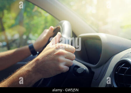 Male hands holding car steering wheel the right way for safe driving - Stock Photo