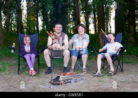 family in forest on picnic, make barbecue, meat co - Stock Photo