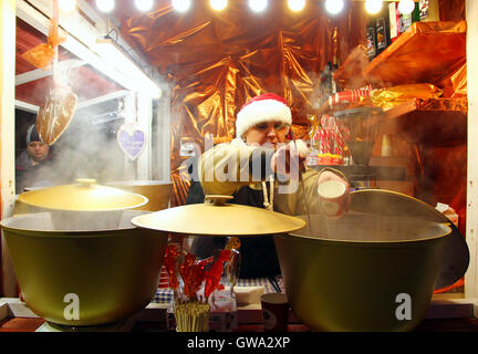 KYIV, UKRAINE - DECEMBER 20, 2015: Woman sell mulled wine at traditional Christmas market on Sophia Square in Kyiv - Stock Photo