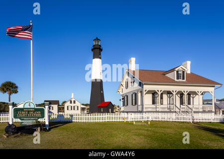 Sunny morning with the American Flag blowing in the wind at Tybee Island Lighthouse on Tybee Island, Georgia - Stock Photo