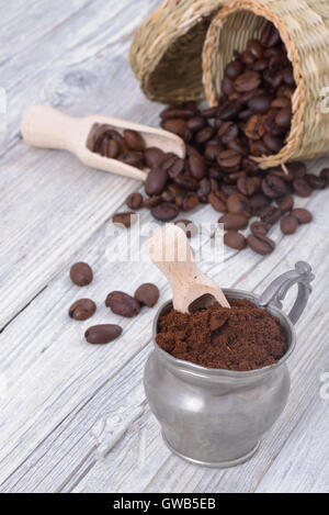 Vintage metal cup with ground coffee on a white wood with coffee beans in the background - Stock Photo
