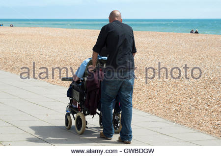 A man pushing an older woman in a wheelchair, Hastings Sea Front, East Sussex, England - Stock Photo