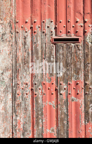 vertical part of old wooden door with letter box and bladdered red paint in sunshine - Stock Photo