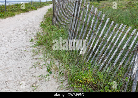 Sandy footpath leading to the beach, and a fence to protect the sand dunes at Ponte Vedra Beach, Florida - Stock Photo