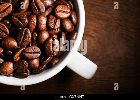 Fresh coffee beans in cup on wooden background - Stock Photo