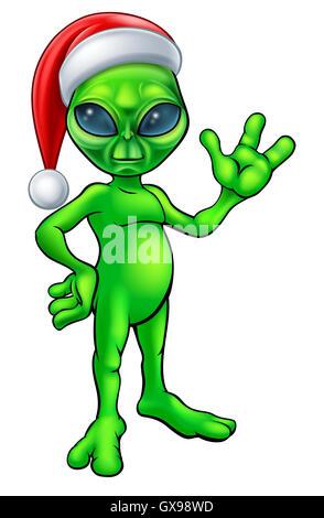 A little Christmas green man alien in a Santa hat cartoon character waving - Stock Photo